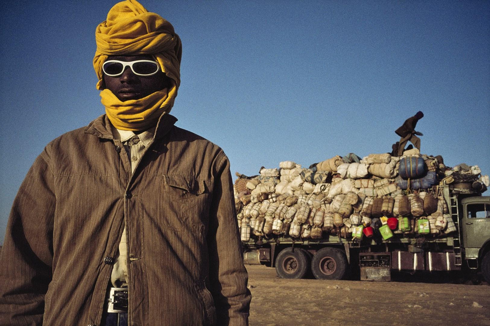 NIGER 2007 : Camions de migrants dans le désert du Ténéré. Des milliers de voyageurs clandestins, partis en majorité du Nigeria, du Niger et du Ghana, chercher du travail en Libye ou dans les pays de l'Union Européenne. Avec le réchauffement climatique et l'accélération de la désertification, le nombre de migrants ne fait qu'augmenter. © Pascal Maitre / Cosmos